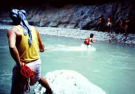 Canyoning: hiking down a river. Crossing the river with a rope
